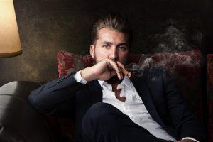 Raucherentwöhnung. Attraktiver Mann raucht genussvoll Zigarre.